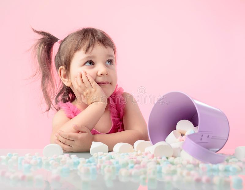 Portrait of a cute little girl with marshmallow on pink background. royalty free stock photos