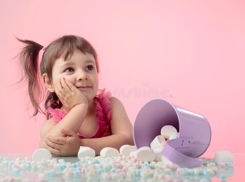 Portrait of a cute little girl with marshmallow on pink background. stock photos