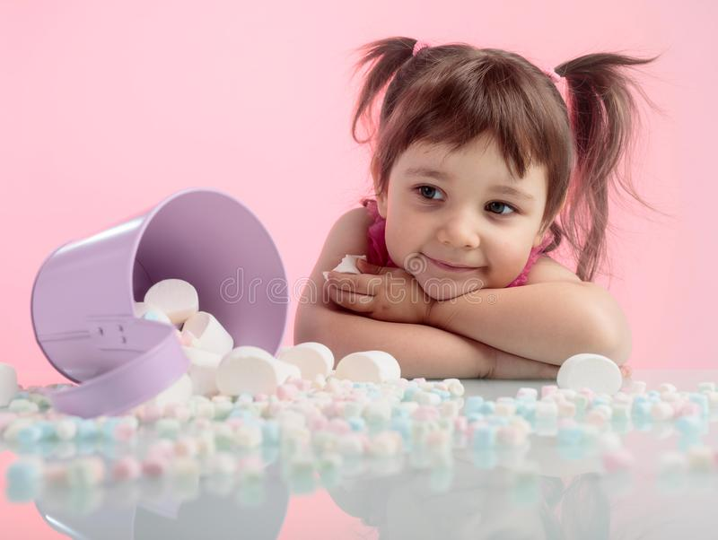 Portrait of a cute little girl with marshmallow on pink background. royalty free stock photography