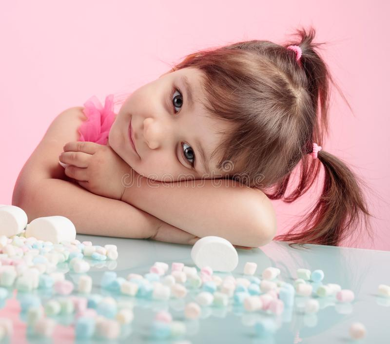 Portrait of a cute little girl with marshmallow on pink backgrou royalty free stock image