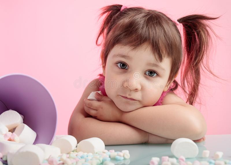 Portrait of a cute little girl with marshmallow on pink backgrou stock image
