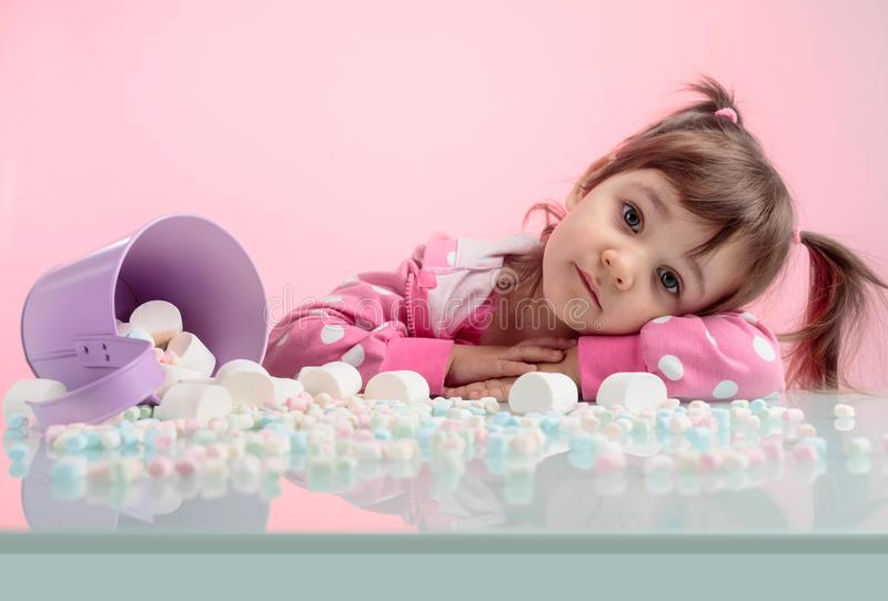 Portrait of a cute little girl with marshmallow on pink background. royalty free stock image