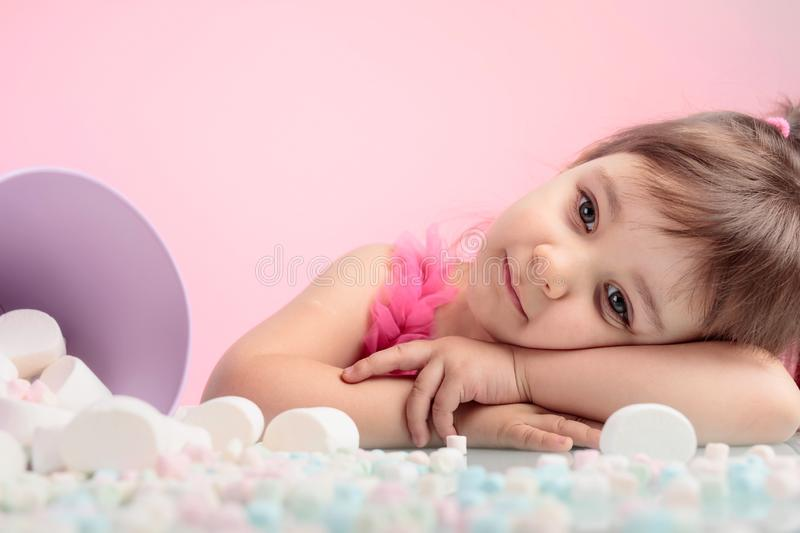 Portrait of a cute little girl with marshmallow on pink background. stock image
