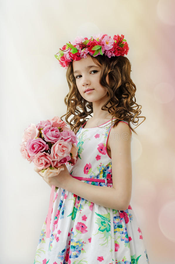 Portrait of cute little girl in nice spring dress, with flowery wreath on head, holds bouquet of flowers. stock photos