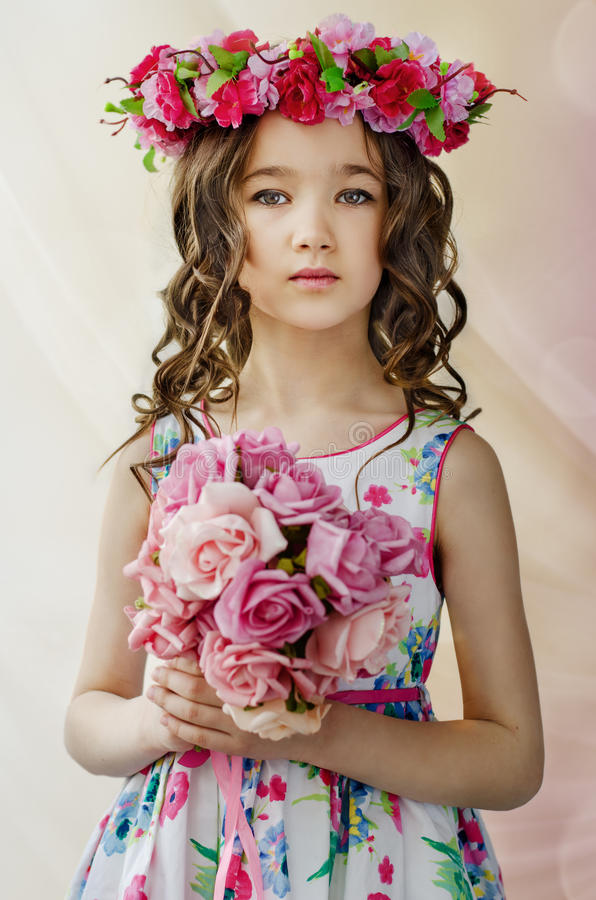 Portrait of cute little girl in nice spring dress, with flowery wreath on head, holds bouquet of flowers. stock photo