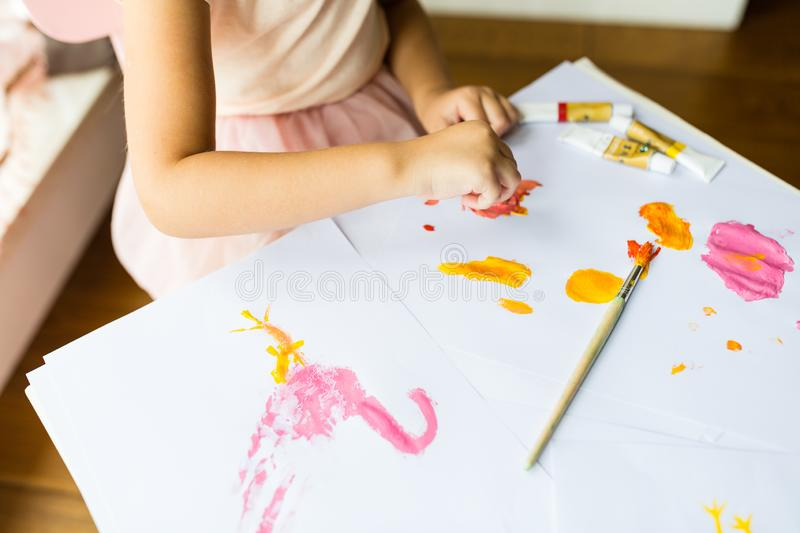 Portrait of a cute little girl painting hands at home. Learn, education, happy childhood concept royalty free stock image