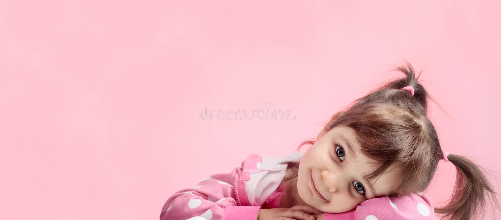 Portrait of a cute little girl with pigtails on pink background royalty free stock images