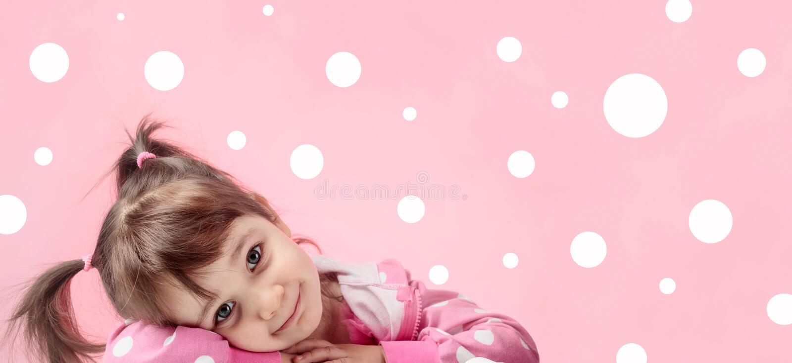 Portrait of a cute little girl with pigtails on pink background. royalty free stock images