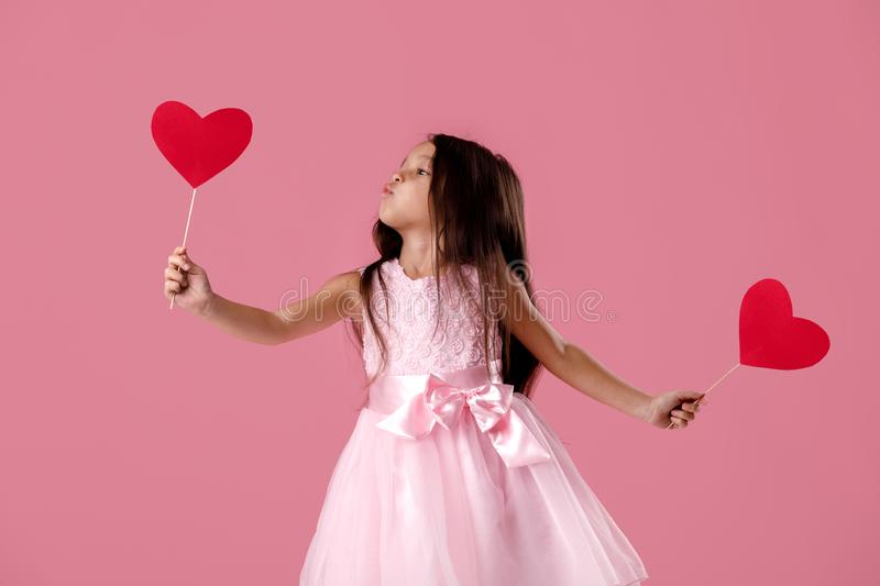 Cute little girl in a pink dress holding a paper heart royalty free stock photos