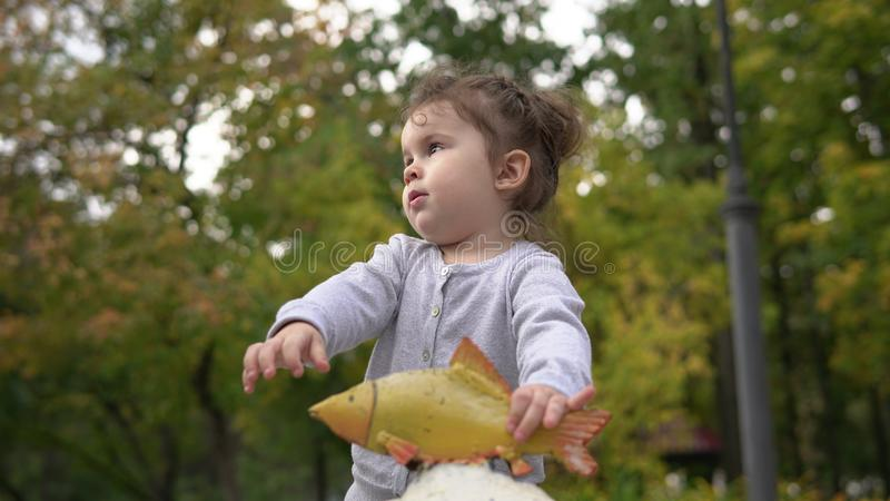 Portrait of cute little girl with gold fish outdoors stock images