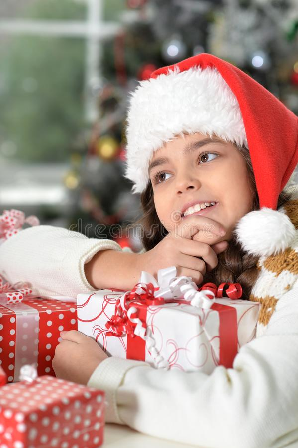 Portrait of cute little girl in Santa hat with gifts for Christmas royalty free stock image