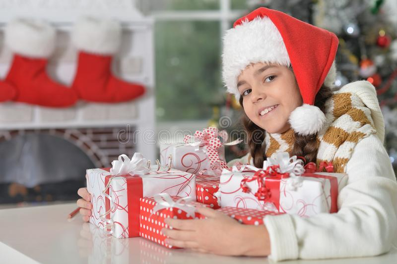 Cute little girl in Santa hat with gifts for Christmas at home royalty free stock photography