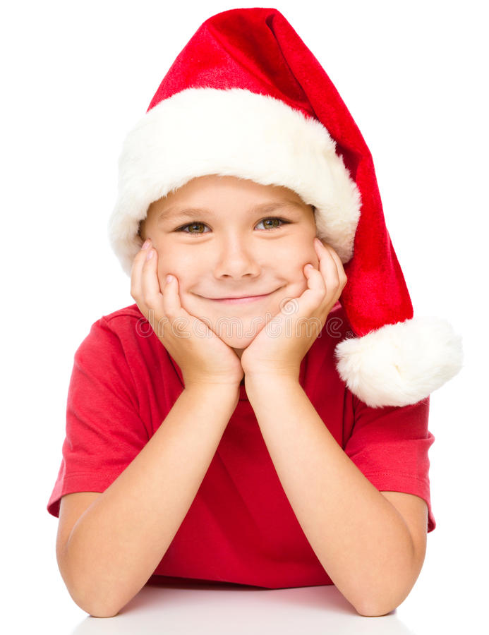 Portrait of a cute little girl in santa hat. Supporting her head with hands, isolated over white royalty free stock photo