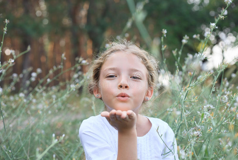 Portrait of a cute little girl sends an air kiss on the nature. stock images