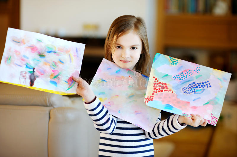 Portrait of cute little girl showing her drawings. Proudly royalty free stock photography