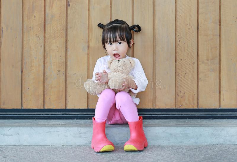 Portrait of cute little girl sit and hugging Teddy Bear against wood plank wall stock photography