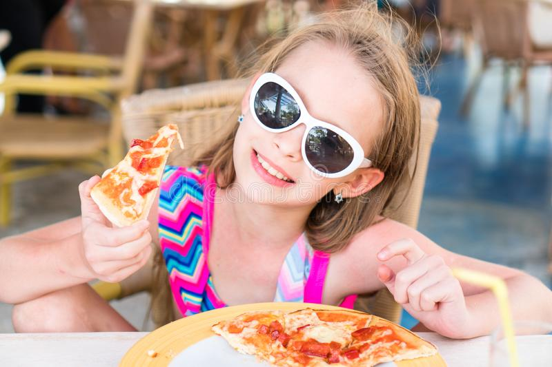 Portrait of cute little girl sitting by dinner table and eating pizza royalty free stock image