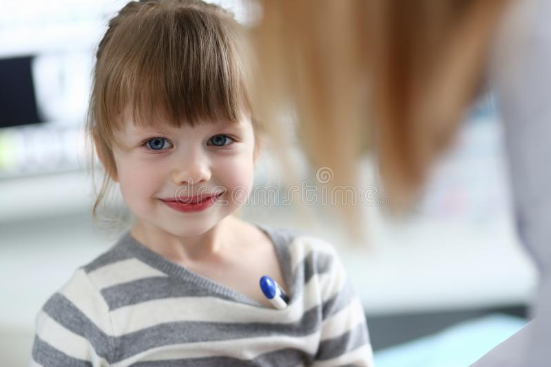 Portrait of cute little girl sitting at doctor office with thermometer stock photo