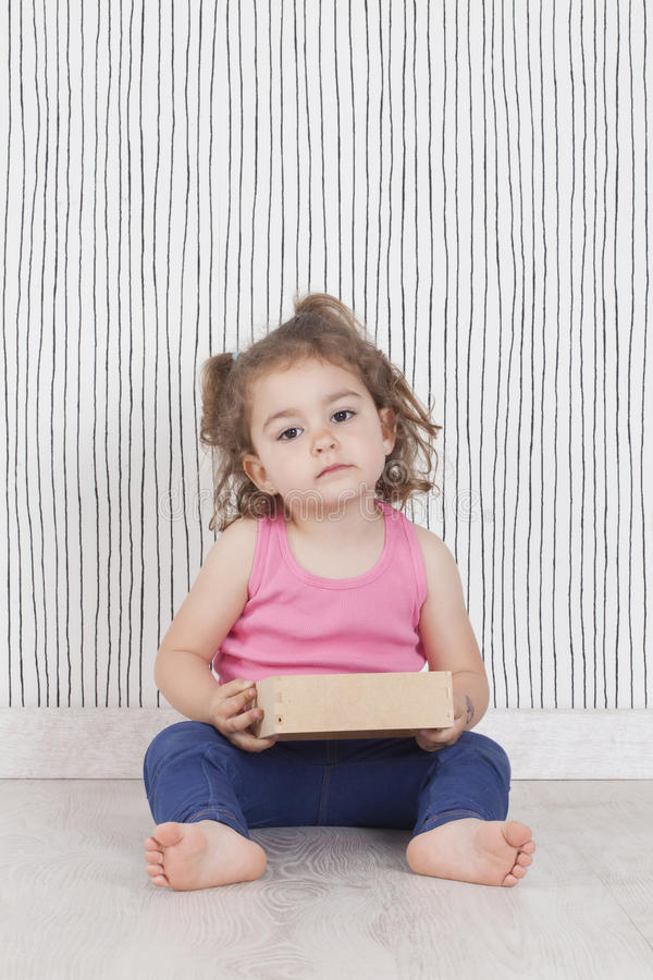 Portrait of cute little girl sitting on floor and holding wooden royalty free stock image