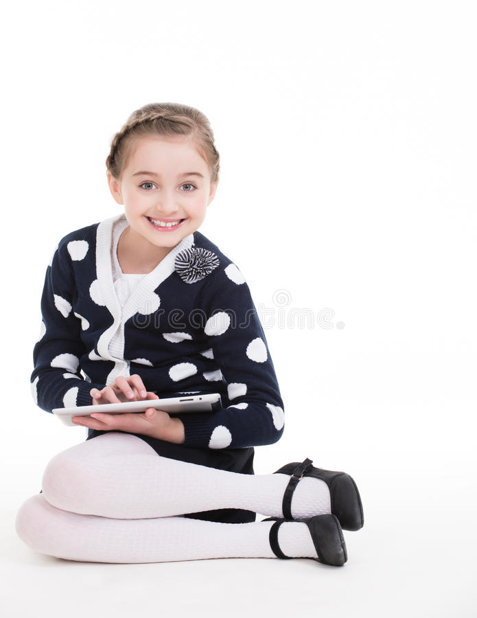 Portrait of cute little girl sitting with the tablet. royalty free stock images