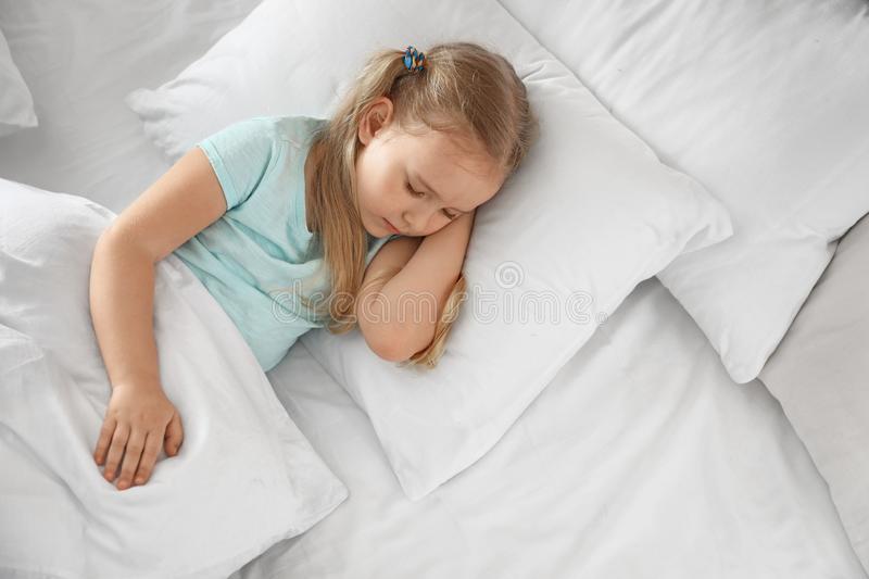 Portrait of cute little girl sleeping in large bed royalty free stock images