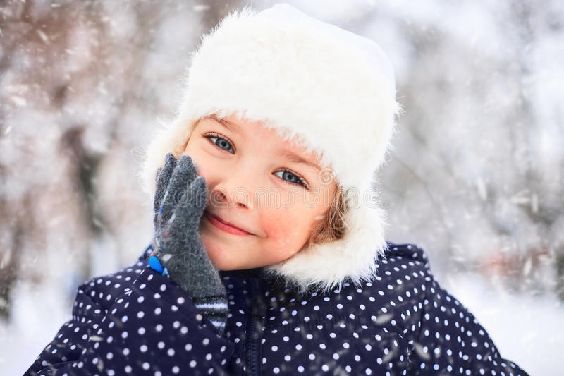 Portrait of a cute little girl in the snowy park. royalty free stock photography