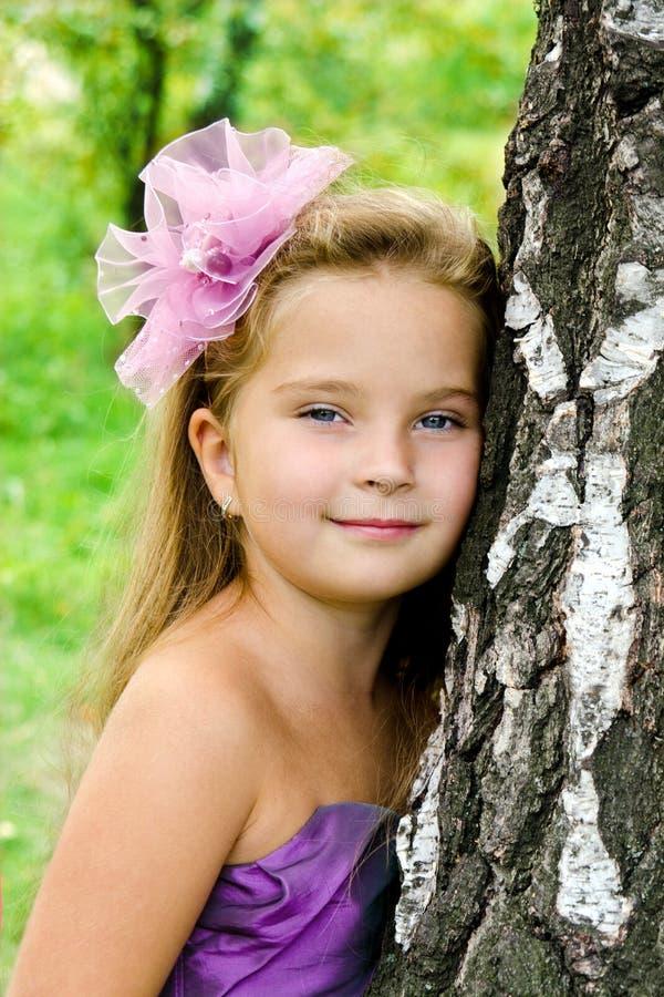 Portrait cute little girl standing near the tree stock photo