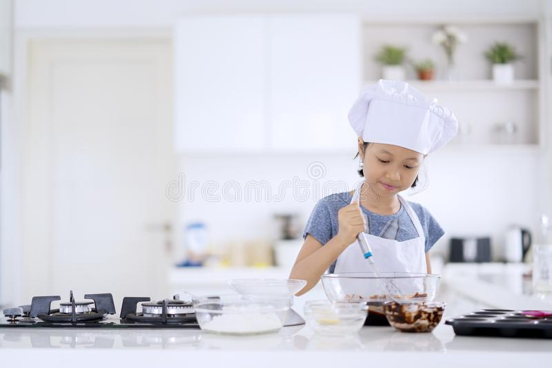 Cute little girl stirring cookie dough stock images