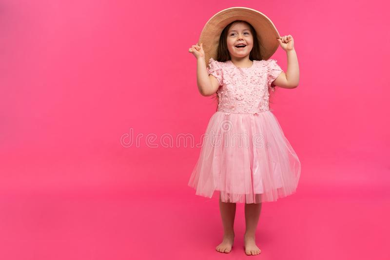 Portrait of cute little girl in straw hat and pink dress in the studio on pink background. Copy space for text. stock photo