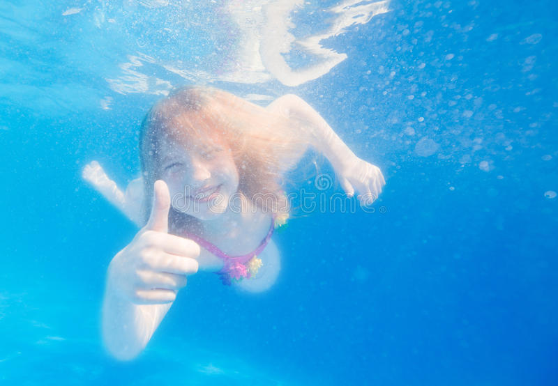 Portrait of a cute little girl swimming underwater royalty free stock images