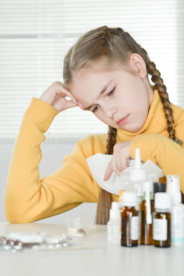 Portrait of a cute little girl taking medicine at home stock images