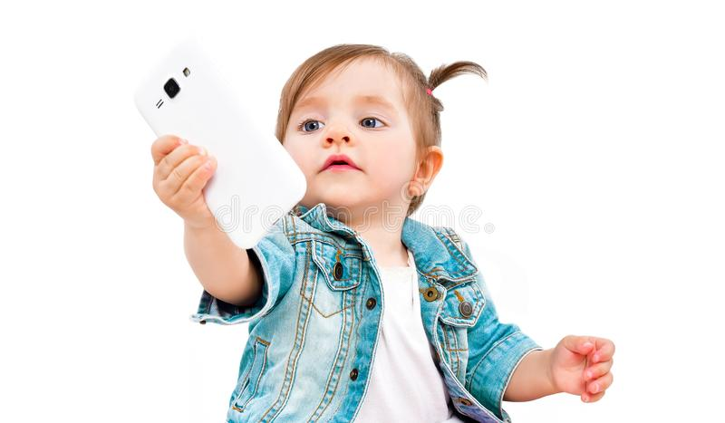 Portrait of cute little girl taking selfie on mobile phone royalty free stock image