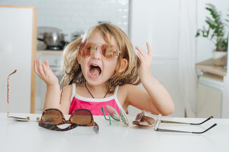 Portrait of cute little girl trying to wear glasses stock photos