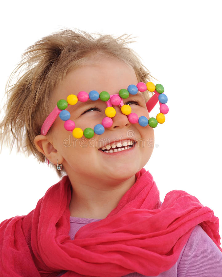 Portrait of cute little girl wearing funny glasses, decorated with colorful sweets, smarties stock photography