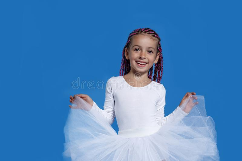 Portrait of a cute little girl in white dress dancing like a ballerina, over blue background. space for text. royalty free stock image