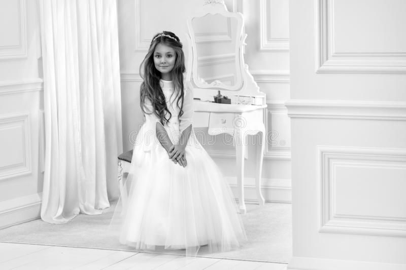 Portrait of cute little girl on white dress and wreath on first holy communion background church gate. Portrait of cute little girl on white dress and wreath on royalty free stock photo