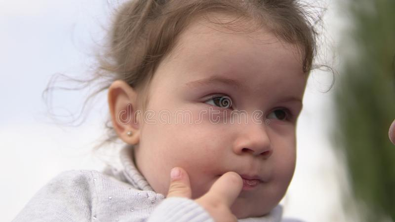 Portrait of cute little girl smiling with finger in mouth outdoors stock photography
