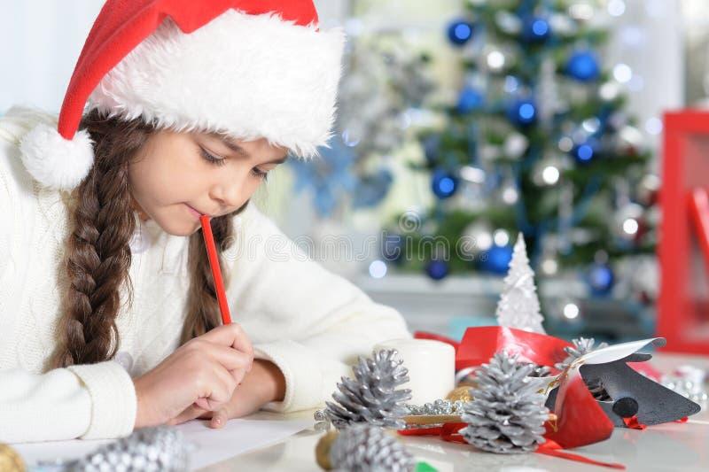 Portrait of cute little girl writing letter stock photo
