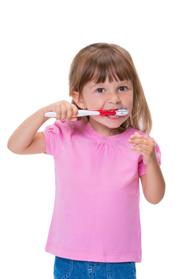 Portrait of cute little girl 3 year old in pink t-shirt brushing her teeth isolated on white background stock images