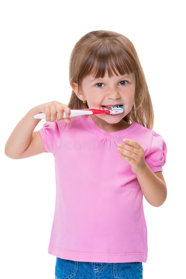 Portrait of cute little girl 3 year old in pink t-shirt brushing her teeth isolated on white background royalty free stock photography