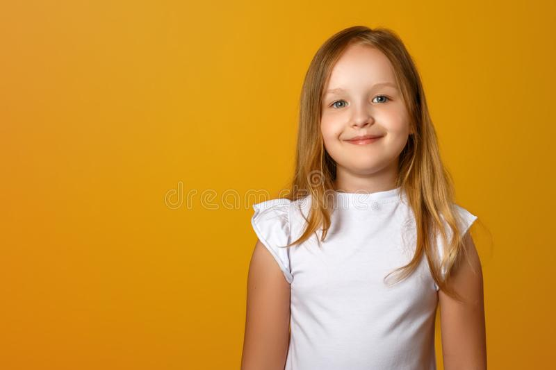 Portrait of a cute little girl on a yellow background. A child blonde is smiling and looking at the camera. royalty free stock photos