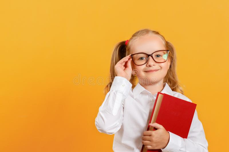 Portrait of a cute little girl on a yellow background. Child schoolgirl looking at the camera, holding a book and straightens royalty free stock photography
