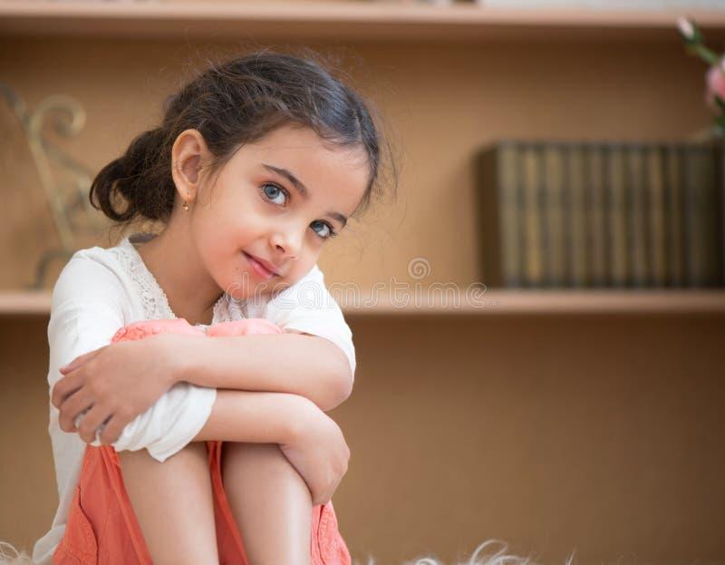 Portrait of cute little hispanic girl. Sittin on carpet at home royalty free stock photos