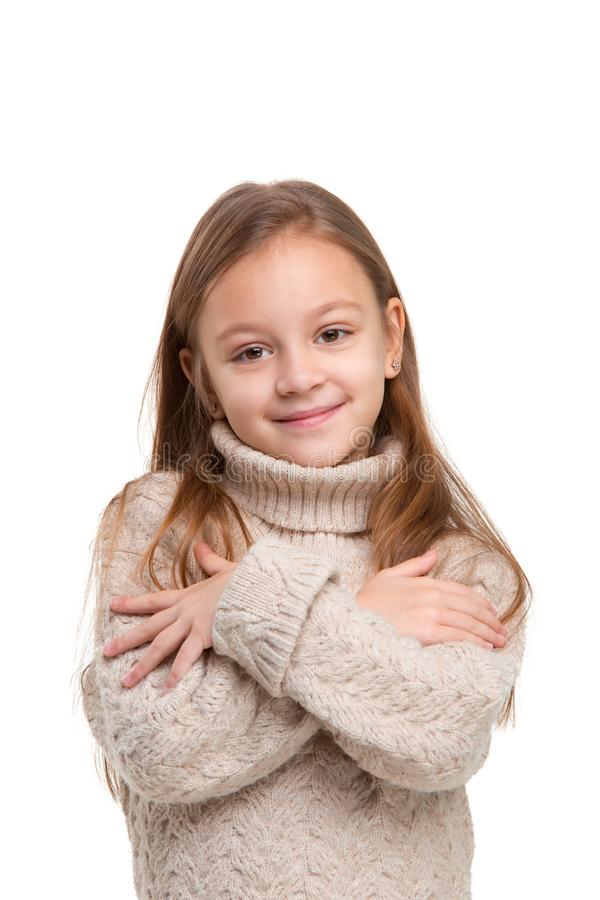 Portrait of cute little kid in stylish knitted sweater looking at camera and smiling stock photo