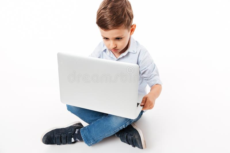 Portrait of a cute little kid using laptop computer. While sitting on a floor isolated over white background stock photo