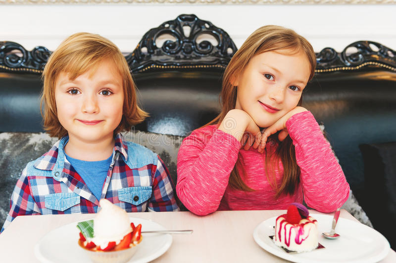 Portrait of cute little kids. Adorable children eating cakes in cafe stock photo