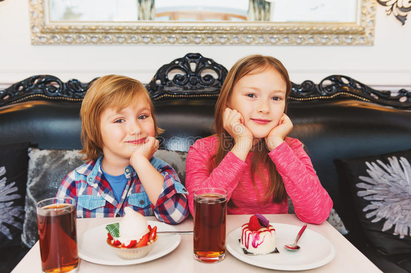 Portrait of cute little kids. Adorable children eating cakes in cafe stock images