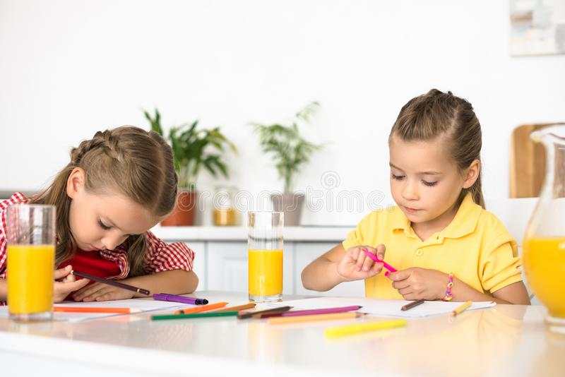 portrait of cute little kids drawing pictures at table stock images