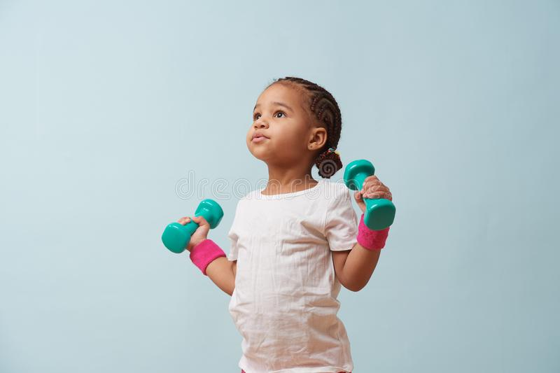 Portrait of cute little mulatto girl lifting dumbbells. Pale blue background stock photos