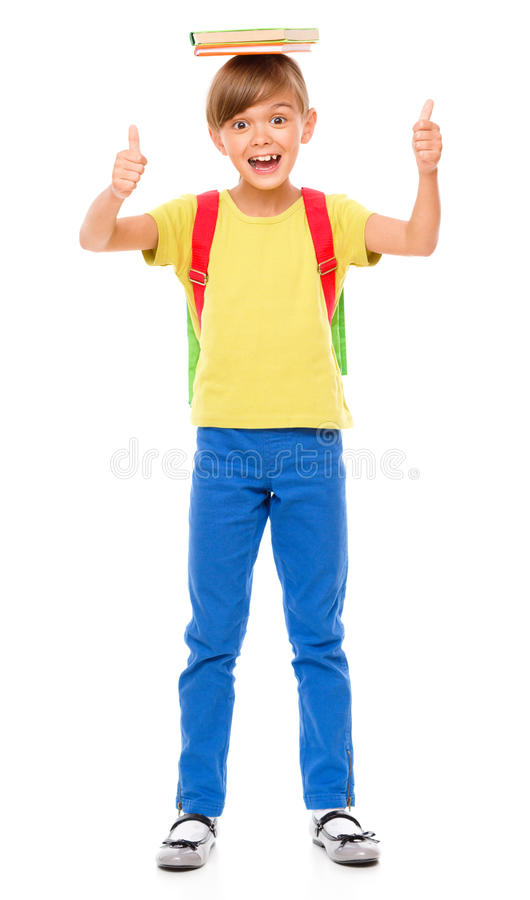 Portrait of a cute little schoolgirl with backpack. Holding book on her head and showing thumb up sign, isolated over white royalty free stock images